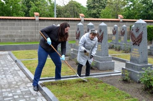 Оксана Комиссарова и Ольга Кондрашина досевают траву на могилах советских солдат